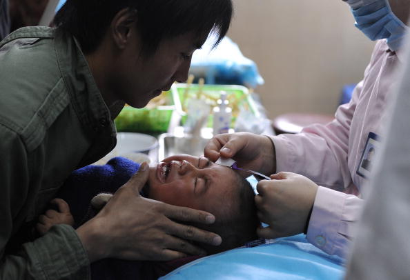 A Chinese man holds his son as a nurse a